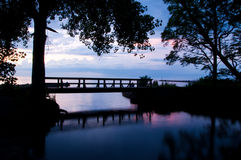 Bridge silhouette at sunset. A small pedestrian bridge and trees silhouetted in a peaceful park on Lake Ontario at sunset stock photo