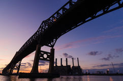 Bridge Silhouette sunset. Bridge and industrial area silhouetted at sunset stock image