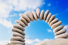 The bridge in the sky. Arch from a sea pebble in morning light and the cloudy sky Royalty Free Stock Image