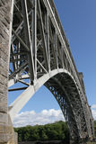 Bridge span. Bridge span with stone tower and metal struts against a blue sky Royalty Free Stock Photography