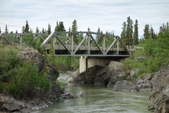 A bridge spanning a large river. A bridge over a swollen river in british columbia Royalty Free Stock Photography