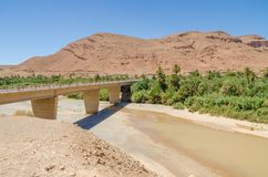 Bridge spanning over dry river bed with some water, mountains and palms in Morocco, North Africa Royalty Free Stock Photo