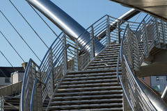 Bridge stairs. A set of stairs with safety railings leading to a bridge made of stainless steel against a blue sky Royalty Free Stock Image