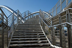 Bridge steps. A set of stainless steel steps leads to a bridge with safety hand railings with a blue sky in the background Royalty Free Stock Photos
