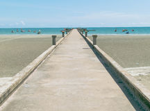 Bridge stone on the beach and sea with blue sky. Royalty Free Stock Image