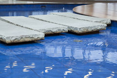 A bridge of stones across the pool with blue water Stock Images
