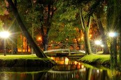 Bridge through a stream in the evening park in the autumn Stock Images