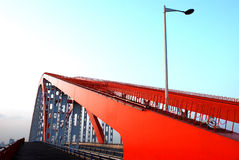 Bridge and street lamp. Orange steel bridge and a street lamp,blue sky Royalty Free Stock Image