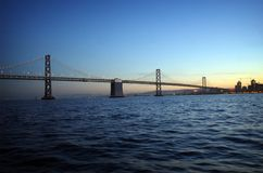 Bridge at Sunset. A suspension bridge over the San Francisco bay leading to a cityscape Stock Photography