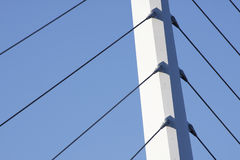 Bridge support against a blue sky. Bridge support with cables against a blue sky stock photo