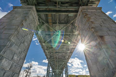 Bridge supported by two columns. Big steel bridge supported by two columns on blue sky with some clouds and sun Royalty Free Stock Photos