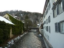 Bridge in Switzerland. Bad Ragaz. Bridge in Bad Ragaz.Switzerland. old house by the river. river with snow-covered banks in winter. European village stock photography