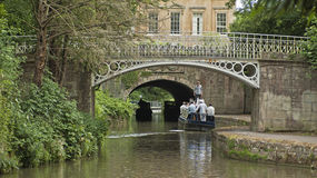 Bridge in Sydney Gardens. A group of friends in a boat in a bay passing under a bridge in Sydney Gardens in Bath Spa, UK Royalty Free Stock Images