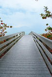 Bridge to Beach. Florida Gulf Coast area with boardwalk over colorful plants in the Fall to the ocean on cloudy day with blue skies Royalty Free Stock Photo