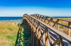 Bridge to the beach sea over sand dune landscape. Wooden footbridge over the sand dunes to the beach of Alcudia bay on Majorca, Spain Mediterranean Sea Stock Photo