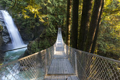 Bridge to Beauty. The suspension bridge looms in front of the massive Cascade Falls, Mission, BC, Canada Stock Image