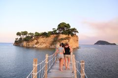 Bridge to Cameo Island, zakynthos, greece. Tourists walking on a small wooden bridge to go to the island of Cameo in the mediterranean sea stock image