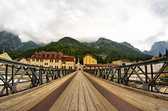 The bridge to the church. The long wooden bridge on the river that leads to the old church of Cave del Predil on the italian Alps Stock Photography