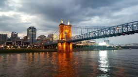 Bridge to Cincinnatti Ohio at dusk. City of Cincinnati, Ohio in the background with the bridge coming into it light up at dusk and reflected on the Ohio river Royalty Free Stock Image