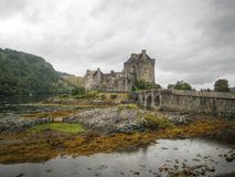 Bridge to Eilean Donan Castle (Scotland, UK). General view of the Eilean Donan Castle and its bridge, during a dark and cloudy day (Scotland, UK Royalty Free Stock Images