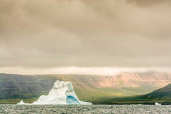 A Lone Iceberg stands winess to the Arctic Tundra. A powerful, solitary iceberg floats off shore with a glacier, green valley behind royalty free stock images