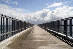 Bridge to infinity. Fences on left and right Royalty Free Stock Photo