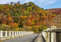 Bridge to Nevytsky Castle hill in autumn. Nevytsky Castle, Ukraine - October 27, 2016: bridge to Nevytsky Castle hill with yellow foliage in autumn forest Stock Images