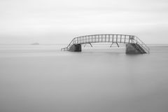 Bridge to nowhere. Long exposure image of bridge surounded by water Royalty Free Stock Photo