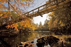 Bridge to tranquility. Bridge over a river with fall colors in the background Royalty Free Stock Photo