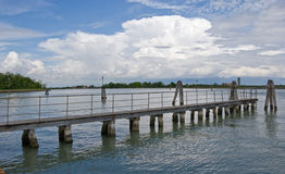 Bridge towards clouds. Wooden bridge towards clouds, Venice canal in Burano, Italy Royalty Free Stock Photography