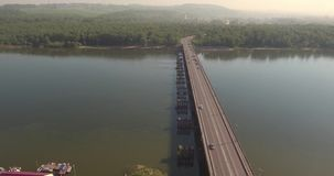 Aerial view. Bridge with traffic over the river w on a sunny day in small city. 4K. Bridge with traffic over the river w on a sunny day in small city stock video
