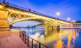 The Bridge of Triana. Seville is divided in two by the river Guadalquivir, and its most famous bridge is the Triana bridge, connecting the historic center to the stock photo