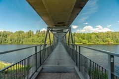 Bridge with underneath walking path crossing a river. Large concrete bridge with underneath walking path crossing the river Dalalven in Avesta, Sweden stock photo