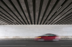 Bridge underpass with blurred red car Stock Photos