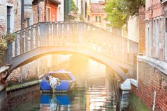 Bridge in Venice. Bridge over a Venetian Canal with a blue boat with solar effect Royalty Free Stock Photo