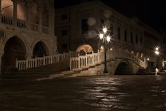 Bridge via the Palace channel, a lamp and a wall of Doges Palace. At night during a rain, Venice stock photos