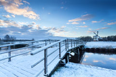 Bridge via river to windmill in winter Stock Photos