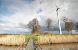 Bridge via river and wind turbine over sky. On Dutch farmland Royalty Free Stock Images