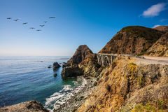 The bridge - viaduct along the Pacific coast. Scenic arch bridge - viaduct runs along the Pacific coast. In the sky flies a flock of cranes. California State Royalty Free Stock Image