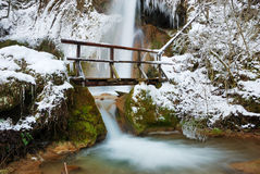 Bridge with Waterfall in Winter. Waterfall with icicles and snow around with a small wooden bridge on a winter day Royalty Free Stock Image