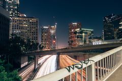 Bridge over highway in Los Angeles. Bridge with white railings and graffiti over  a  multi-lane highway through Los Angeles at night with traffic trails, and Stock Photo