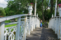 Bridge wiggle railings and girl resting at bridge. Old wooden bridge with white wiggle railings and girl resting at the end of bridge Stock Photo