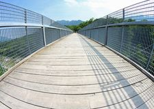 Bridge with a wooden walkway and handrail made of galvanized ste Royalty Free Stock Images