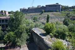 Bridge in Yerevan. Ruins of the medieval brodge with the Noy brewery and a building in the far Stock Photos