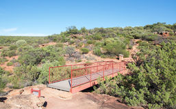 Bridge in Z-bend Cliffs. Bridge connecting the red sandstone cliffs at the Z-bend lookout in Kalbarri National Park with native greenery under a clear blue sky Stock Image
