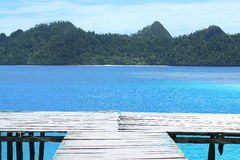 Bridgehead to the Blue. The end of a wooden bridge to a crystal clear blue water and a part view of karst island in background (Wayag Karst Archipelago, Raja Stock Image