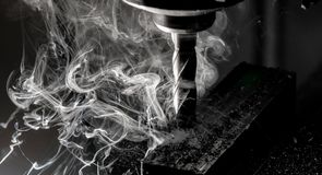 CNC end mill finishing a stack of steel plate with metal filings chips and heavy smoke royalty free stock photography