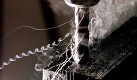Bridgeport CNC-Schaftfräser, der einen Stapel der Stahlplatte mit Metallarchivierungschips und dem mäßigen Rauchschleppen beendet lizenzfreies stockbild