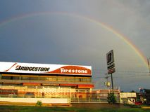 Bridgestone Firestone tire store. In Puerto Ordaz , Venezuela , South America , with a rainbow and gray clouds in the background Royalty Free Stock Photos