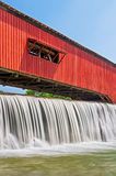 Bridgeton Covered Bridge and Waterfall. Water falls over the mill dam at the historic red covered bridge in the Parke County, Indiana town of Bridgeton Royalty Free Stock Photography